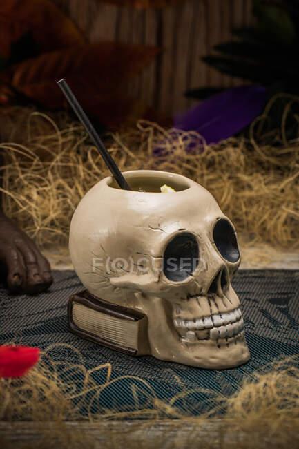 Cráneo de taza tiki polinesia cerámica en forma de paja colocada en medio de hierba seca con valla de madera y plumas de colores sobre fondo borroso - foto de stock