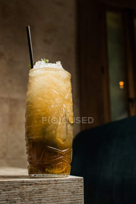 Tiki cup with cold alcohol drink with straw served with ice and decorated with fresh herb placed on blurred background — Stock Photo
