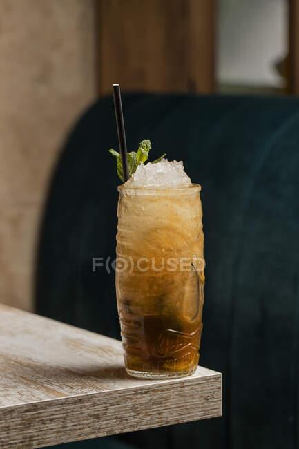 Copa Tiki con bebida alcohólica fría con paja servida con hielo y decorada con hierba fresca colocada sobre fondo borroso - foto de stock