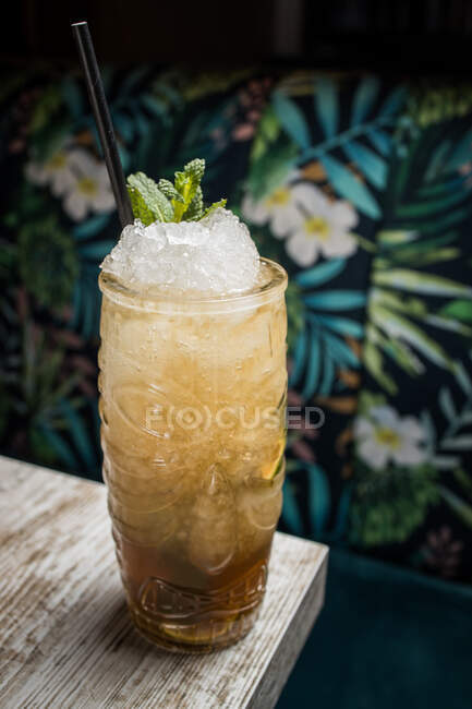 Desde arriba de la taza tiki con bebida fría de alcohol con paja servida con hielo y decorada con hierba fresca colocada sobre fondo borroso - foto de stock