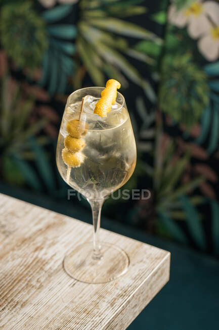From above of crystal wineglass with Martini cocktail served with lemon zest and olives edge of wooden table — Stock Photo