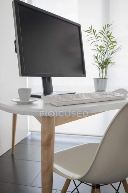 Modern computer with black monitor and white keyboard placed on desk with potted green plant and coffee mug in office — Stock Photo