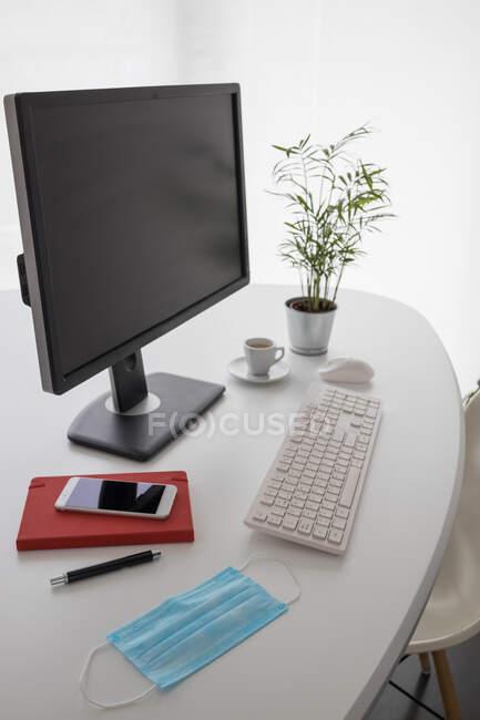Ordinateur moderne et smartphone avec ordinateur portable placé sur une table blanche avec masque médical et plante en pot dans un bureau léger — Photo de stock
