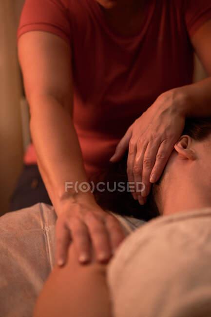 Cultivo masajista irreconocible amasar hombros de la señora feliz durante la sesión de spa en el salón - foto de stock