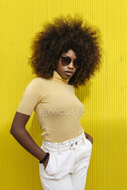 Junge ethnische Frau mit Afro-Frisur und Sonnenbrille steht auf gelber Wand — Stockfoto