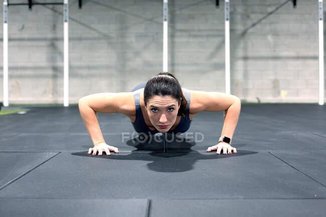 Fuerte determinado joven deportista haciendo flexiones durante el entrenamiento funcional intenso en el gimnasio - foto de stock