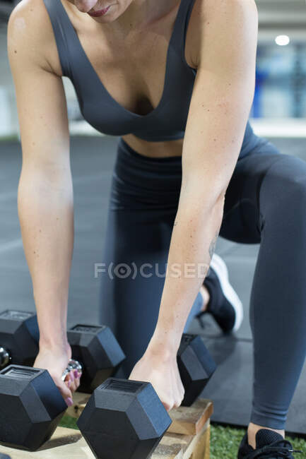 Неузнаваемая спортсменка, собирающая тяжёлые гири при подготовке к упражнениям в весе во время функциональной тренировки в спортзале — стоковое фото