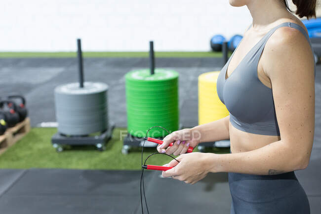 Crop unrecognizable slim female in sportswear doing exercise with jumping rope during functional workout in sports club — Stock Photo