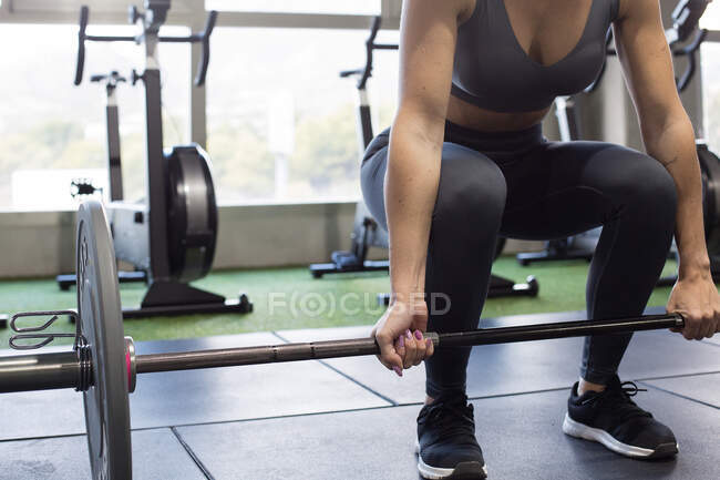 Crop anonymous female athlete lifting heavy barbell during intense functional workout in gym with modern equipment — Stock Photo