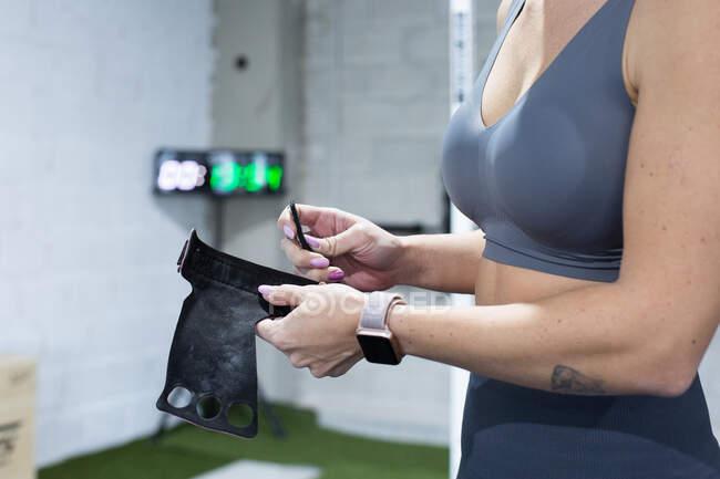 Vista lateral da colheita atleta feminina anônima em relógio inteligente segurando pulseira enquanto se prepara para o treinamento intenso em ginásio — Fotografia de Stock