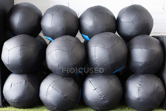 Набір чорних лікарських кульок для функціональної підготовки складений рядами біля стіни в сучасному спортивному клубі. — стокове фото