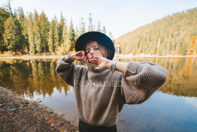 Young blond cool female tourist in trendy apparel looking at camera while standing on coast against water reflecting trees — Stock Photo