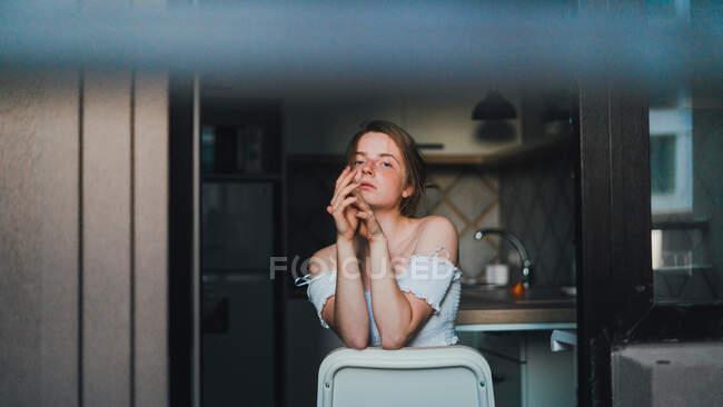 Unemotional giovane femmina con top con spalle nude seduto sul bancone della cucina e guardando la fotocamera con calma — Foto stock