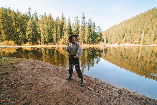 Young cool female tourist in trendy apparel looking away while standing with hand in pocket on coast against water reflecting trees — Stock Photo