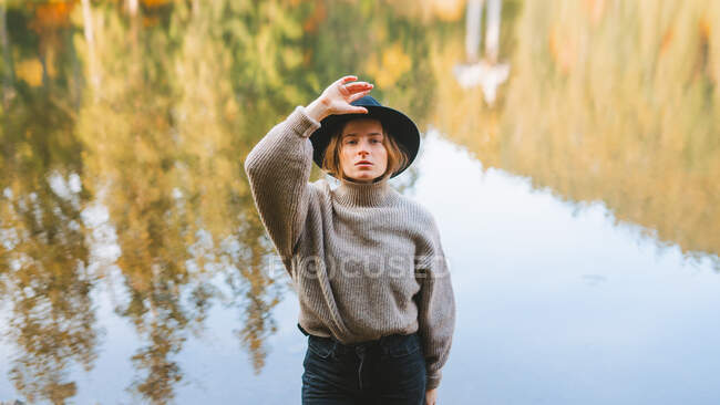 From above young blond cool female tourist in trendy apparel looking at camera while standing on coast against water reflecting trees — Stock Photo