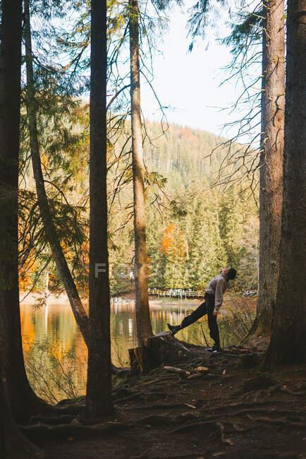 Вид сбоку на анонимную женщину-туристку, откинувшуюся на грубом побережье к воде, отражающей осенние деревья на горе — стоковое фото