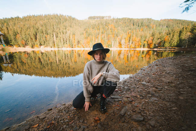 Young cool female tourist in trendy apparel looking at camera from dry coast against transparent water reflecting autumn trees — Stock Photo