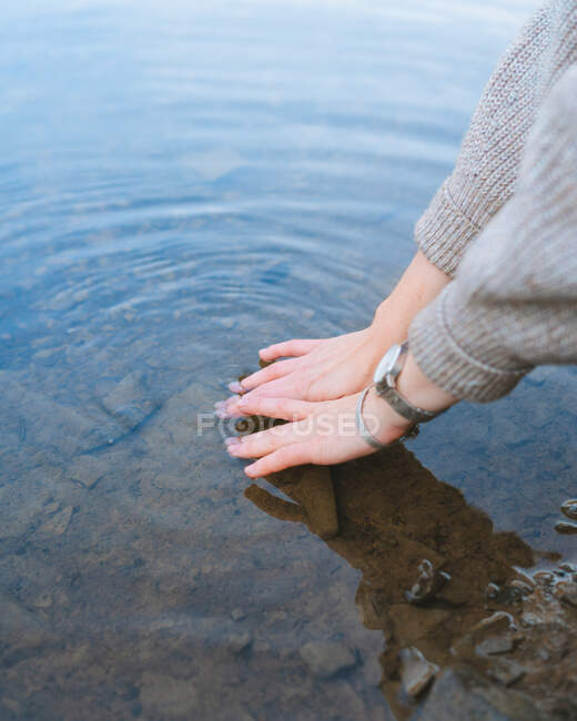 Geschnitten unkenntlich Reisenden Berührung reinen Seewassers vom Ufer — Stockfoto