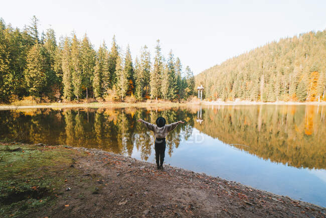 Back view of anonymous female tourist in hat with raised arms admiring transparent water against autumn trees on mount — Stock Photo