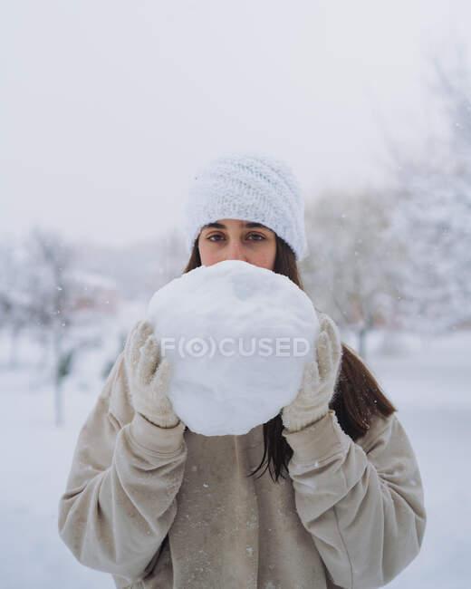 Jeune contenu ethnique femelle en bonnet tricoté montrant boule de neige sous le ciel blanc dans le parc de Madrid — Photo de stock