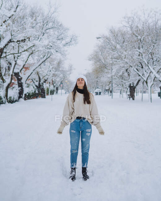 Young happy female standing on winter snow park with white trees in Madrid with eyes closed — Stock Photo