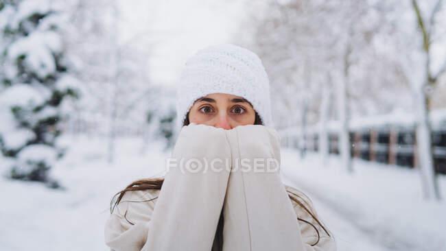 Jovem anônimo surpreendido fêmea em malha chapéu cobrindo rosto enquanto olha para a câmera no caminho entre as árvores na Espanha — Fotografia de Stock