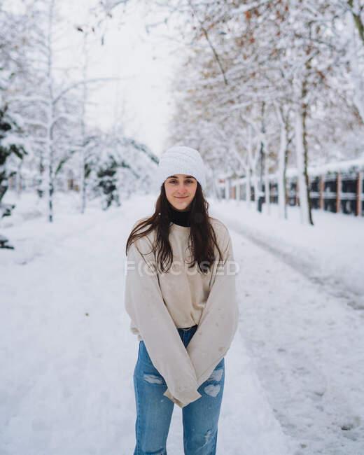 Молодая женщина, стоящая на прямой дороге со снегом под белым небом в Мадриде, смотрит в камеру — стоковое фото