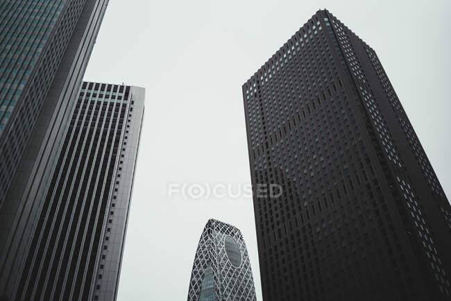 Vista a altas torres de rascacielos y pequeños edificios en la gran ciudad - foto de stock