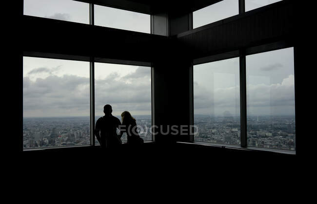 Silhouettes of unrecognizable tourist people admiring skyline views from high skyscraper in tokyo — Stock Photo