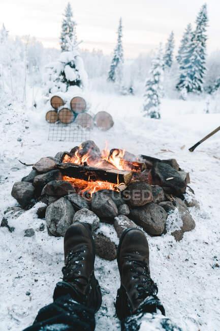 Cultivez un voyageur anonyme en bottes chaudes reposant près d'un feu de joie sur un terrain enneigé près d'une forêt de conifères en hiver. — Photo de stock
