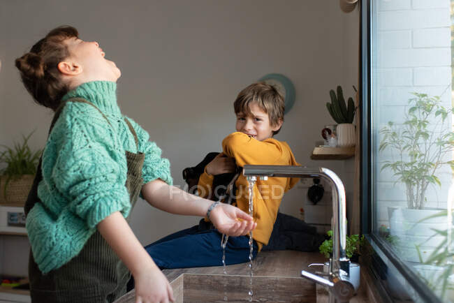 Side view of carefree siblings playing near sink in kitchen while having fun at home at weekend — Stock Photo