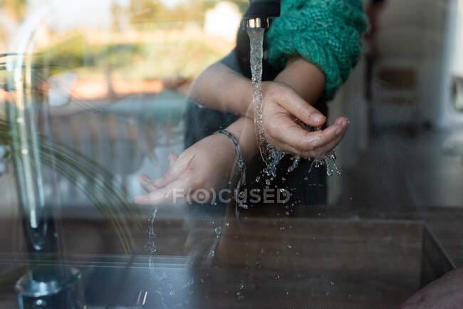 Through glass of crop unrecognizable kid washing hands under running water in sink in kitchen — Stock Photo