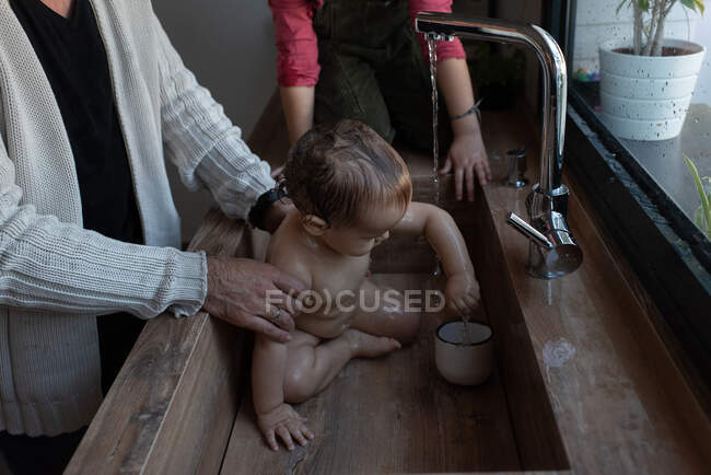 Cropped unrecognizable little girl washing cute baby in arms of father during bathing in sink in kitchen — Stock Photo