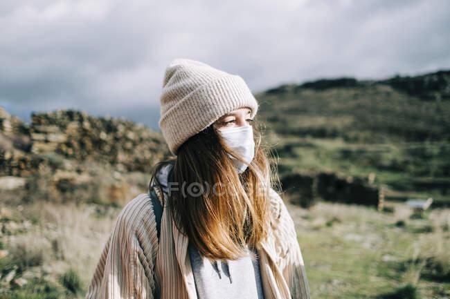 Анонімні мрійливі жінки-туристки, які дивляться на маску обличчя, милуючись зеленими насипами на сонці під час пандемії COVID 19 — стокове фото