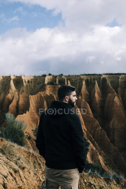Back view of male tourist admiring ravine from mount under cloudy sky in daylight — Stock Photo