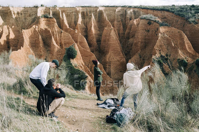 Unrecognizable female traveler pointing at gorge near friends talking on dry terrain with grass during trip in Spain — Stock Photo