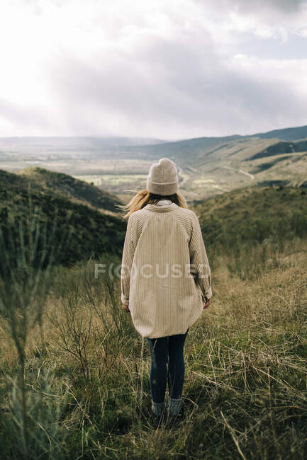 Back view of faceless tourist standing on grass while contemplating mountain under cloudy sky in Europe — Stock Photo