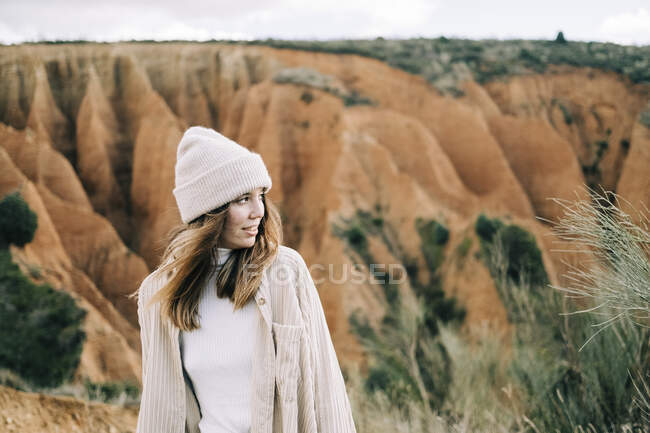 Young happy female traveler standing against mounts in sunlight looking away — Stock Photo