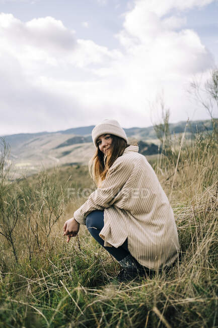 Side view of young content female tourist in warm clothes squatting on grass against ridge while looking at camera — Stock Photo