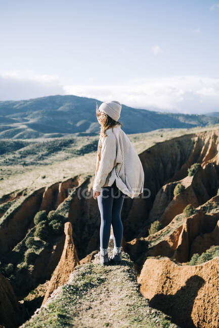 Side view of unrecognizable female tourist standing with eyes closed on gorge contemplating green mountains in Spain — Stock Photo