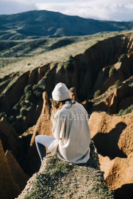 Back view of unrecognizable female tourist contemplating green mountains while resting on gorge in Spain — Stock Photo