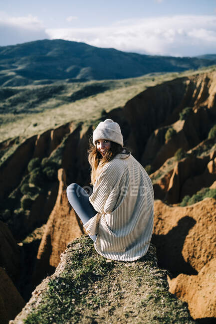 Back view of female tourist looking over the shoulder while sitting on gorge contemplating green mountains in Spain — Stock Photo