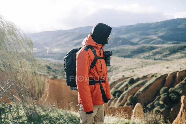 Side view of unrecognizable male trekker in outerwear with rucksack contemplating mountains in back lit — Stock Photo