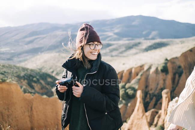 Alegre turista femenina con el pelo volador mirando hacia otro lado cerca de la cosecha socio anónimo en la garganta contra el monte a la luz del sol - foto de stock