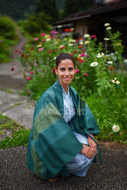 Portrait of young attractive caucasian woman in a traditional Japanese kimono surrounded by flowers in small village of Ainokura, Japan — Stock Photo