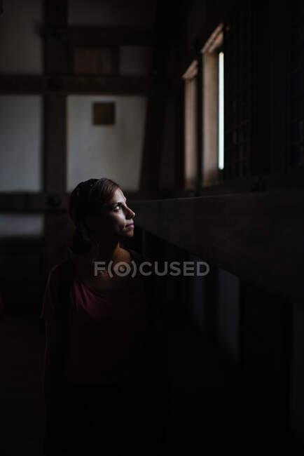 Mujer caucásica joven mira a través de la ventana en el castillo de Himeji, Japón. Su cara está iluminada por la luz natural que entra. - foto de stock