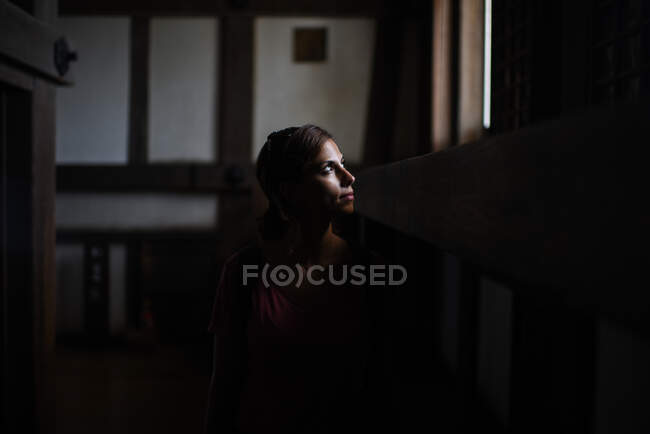 Young caucasian woman looks through window in Himeji Castle, Japan. Her face is lit by natural light that comes in. — Stock Photo