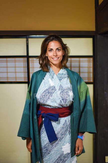 Interior retrato de ajoelhar feliz jovem mulher caucasiana atraente vestindo um quimono japonês tradicional dentro de uma casa, Ainokura, Japão — Fotografia de Stock
