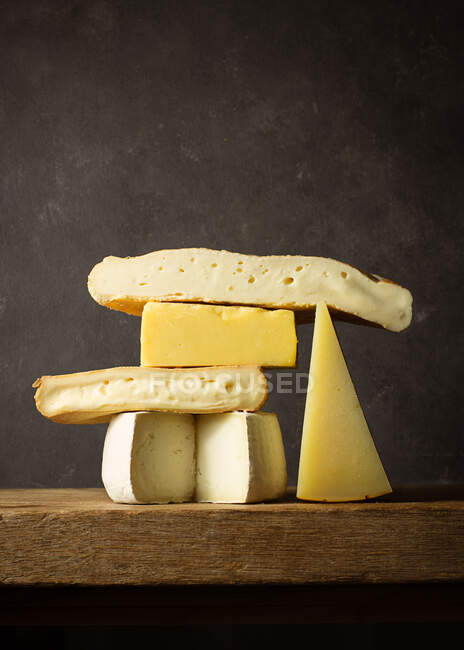 Various cut cheese on wooden board placed on wooden table — Stock Photo