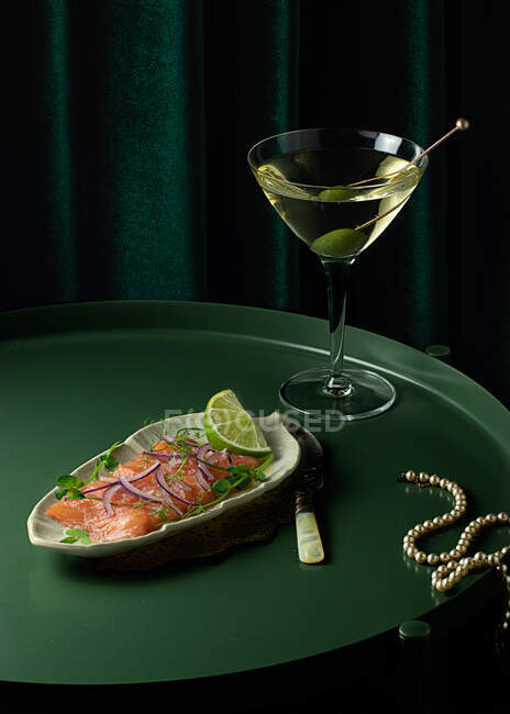 From above of appetizing smoked salmon slices served on plate with lime and onion and placed on round table with glass of vermouth with olive near elegant pearl necklace — Stock Photo